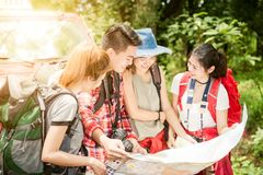 Hiking - hikers looking at map. Couple or friends navigating together smiling happy during camping travel hike outdoors in forest. Stock Image