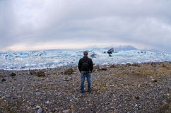 Hiking in Iceland. Man with backpack standing on shore at Jokulsarlon Glacier lagoon in southern Iceland Royalty Free Stock Photography