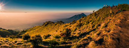 Hiking in Indonesia. Panoramic photo of mountains surrounding Mount Merbabu and hikers at top during sunrise near Yogya in central Java province in Indonesia. In Royalty Free Stock Images