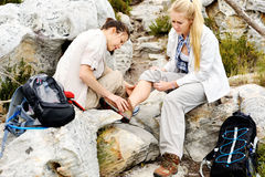 Hiking injury ankle. A women has sprained her ankle while hiking, her friend uses the first aid kit to tend to the injury royalty free stock photo