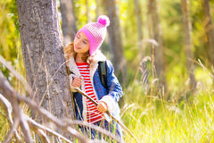 Hiking kid girl with backpack in autum poplar forest Royalty Free Stock Photos