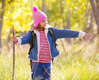 Hiking kid girl with backpack pointing finger in autum forest Royalty Free Stock Photos