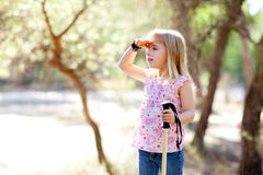 Hiking kid girl searching hand in head in forest. Outdoor stock photography