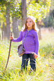 Hiking kid girl with walking stick in autum poplar forest Royalty Free Stock Image