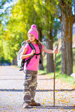 Hiking kid girl with walking stick and backpack in autumn Stock Photo