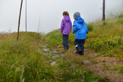 Hiking kids. Siblings in rainy weather clothed in waterproof jackets and trousers. Walking on a beaten boggy track in the mountains. The path is lined by Stock Photo