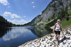 Hiking at Lahngangsee, Austria. Woman walking along Vorderer Lahngangsee lake in Totesgebirge - Austria Stock Photo