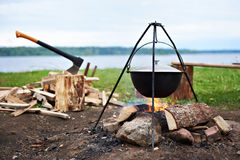 Hiking landscape with bonfire, pot and ax Royalty Free Stock Photography