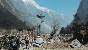 Ghodatabela, Nepal - March 28, 2018: tourists climb the mountains. Hiking In Langtang. people with backpacks go to the mountains through a ruined settlement stock footage