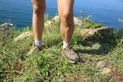 Hiking legs with injured knee on seaside mountain Royalty Free Stock Photos