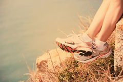 Hiking  legs sit seaside rock Royalty Free Stock Photography