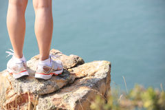 Hiking legs stand seaside rock Stock Image