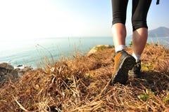 Hiking legs walking on seaside mountain Stock Images
