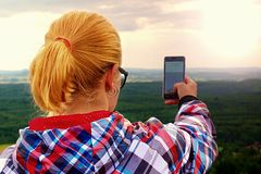 Hiking long hair blonde woman taking photo with smart phone at mountains. Stock Images