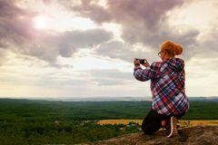 Hiking long hair blonde woman taking photo with smart phone at mountains. Royalty Free Stock Images