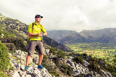 Hiking man checking direction in mountains Stock Images
