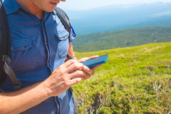 Hiking man checking direction in mountains. Hiking man checking direction in mountains by smartphone Royalty Free Stock Photos