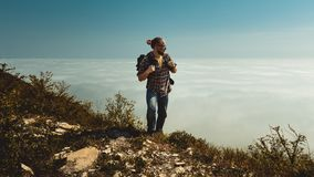 Hiking Man climbing to the top and looks to the side of the clouds. Motivation, travel, search, scout, wanderlust, tourism concept royalty free stock image