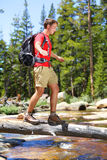 Hiking man hiker crossing river in Yosemite. Hiking man crossing river in walking in balance on fallen tree trunk in Yosemite landscape nature forest. Happy male Stock Image