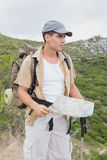 Hiking man holding map on mountain terrain Royalty Free Stock Photography