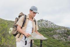 Hiking man holding map on mountain terrain Stock Photos