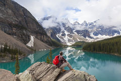 Hiking Man Looking Moraine Lake & Rocky Mountains. Hiking man sitting on rock with rucksack backpack by Moraine Lake looking at snow covered Rocky Mountain peaks Stock Photos