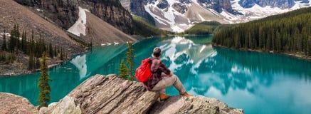 Hiking Man Looking at Moraine Lake & Rocky Mountains Panorama stock photo