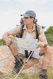 Hiking man with map on mountain terrain Royalty Free Stock Photography