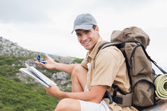 Hiking man with map on mountain terrain Stock Image