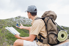 Hiking man with map on mountain terrain Royalty Free Stock Photos