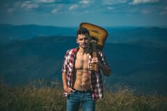 Hiking man. Motivated hiker with guitar looking at beautiful view. Trekking, travel and tourism concept. Fitness and