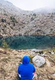 Hiking man in the mountains relaxing in front to a silent lake i stock photography