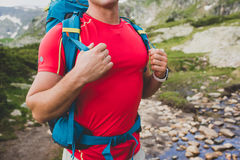 Hiking man portrait with backpack walking in nature. Caucasian man holding hands on backpack, hiking near the river Stock Image