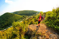 Hiking man portrait with backpack walking in nature. Caucasian man smiling happy with forest and mountains in background Royalty Free Stock Photo