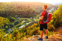Hiking man portrait with backpack walking in nature. Caucasian man smiling happy with forest and mountains in background Stock Images