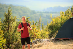 Hiking man portrait with backpack walking in nature. Caucasian man smiling happy with forest and mountains in background Stock Photos