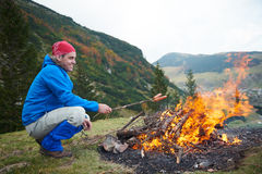 Hiking man prepare tasty sausages on campfire Royalty Free Stock Photos