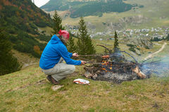 Hiking man prepare tasty sausages on campfire Stock Images