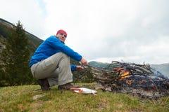 Hiking man prepare tasty sausages on campfire Stock Image
