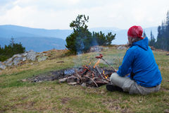 Hiking man prepare tasty sausages on campfire Royalty Free Stock Image