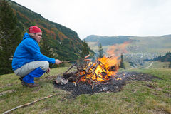 Hiking man prepare tasty sausages on campfire Stock Photo