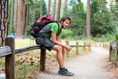 Hiking man resting with backpack in forest park Stock Photo
