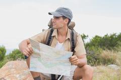 Hiking man sitting with map on mountain terrain Stock Photos