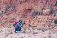 Hiking man take a photo with camera. Climber or trail runner in mountains, inspirational landscape. Motivated hiker with red backpack looking at beautiful view royalty free stock photo