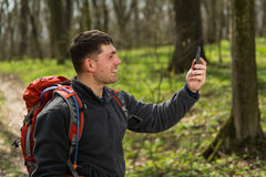 Hiking man take selfie during his walk through the forest. Hiking man with red backpack take selfie during his walk through the forest Royalty Free Stock Photo