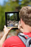 Hiking man taking nature pictures on tablet Royalty Free Stock Image