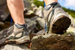 Hiking man with trekking boots on the trail. Closeup of male feet on hiking. Active life concept stock images
