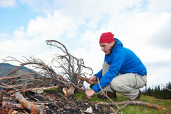 Hiking man try to light fire Stock Image