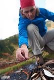 Hiking man try to light fire Stock Images
