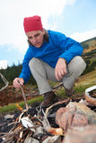 Hiking man try to light fire Stock Photography
